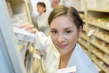 Jeune femme souriante en pharmacie rangeant des médicaments avec collègues en fond