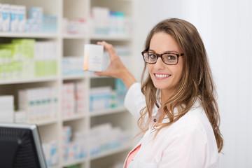 Jeune femme en pharmacie souriant et tenant un produit